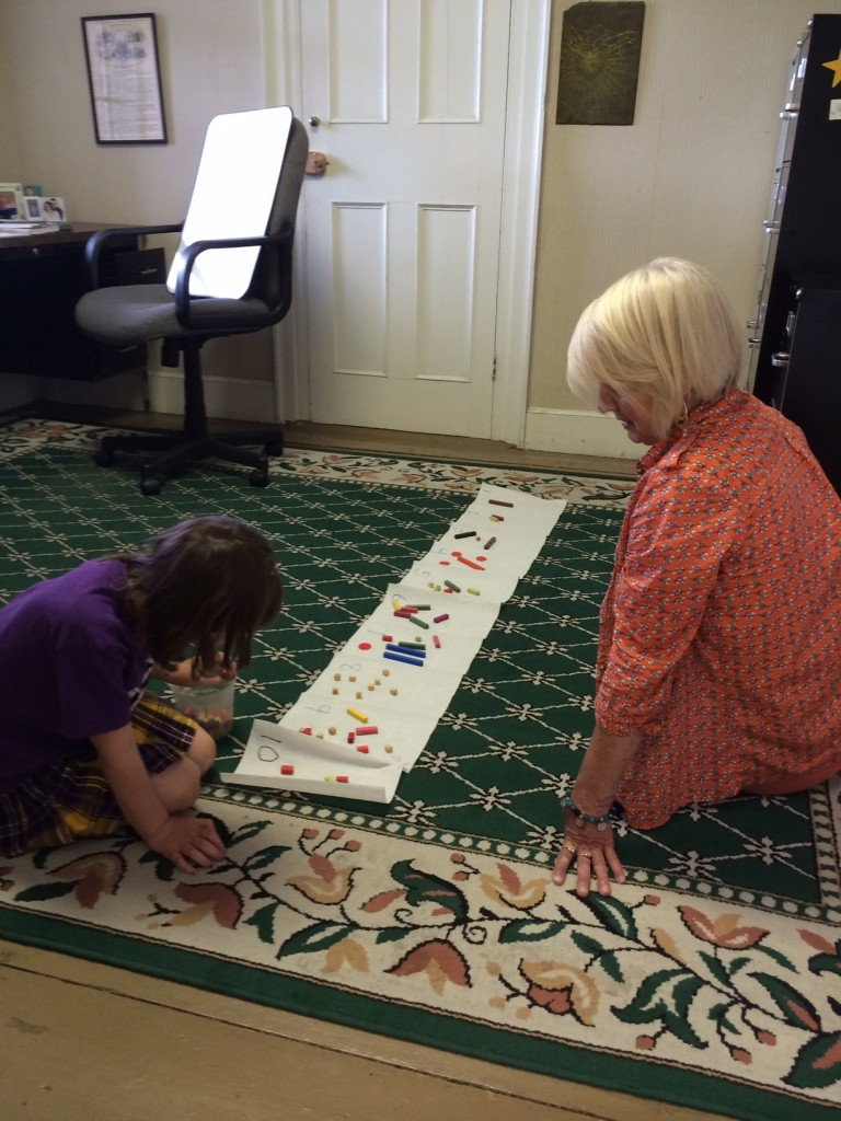 Isabella Frost uses cuisenaire rods to practice number facts, under the watchful eye of tutor Gano Stevens.